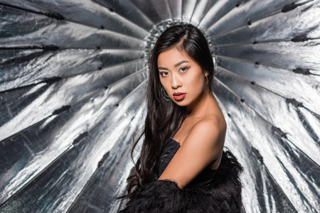 beautiful asian woman wearing ostrich feathers coat and looking at camera