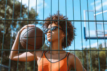 young african-american woman in sports bra and sunglasses holding a basketball ball on her shoulder, posing behind wired fencing Stock fotó