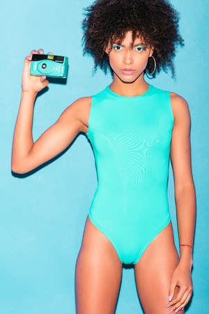 attractive afro girl posing in blue swimsuit with vintage photo camera, isolated on turquoise