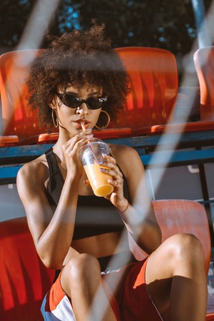 Young african-american woman in sportive attire sitting in the bleachers and drinking orange juice