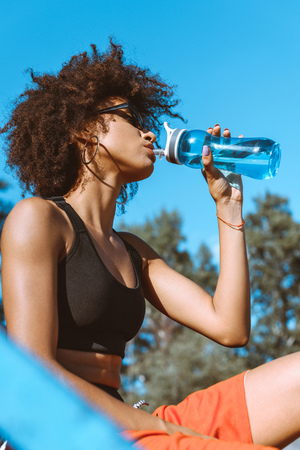 Young african-american woman in sportive attire drinking from blue water bottle