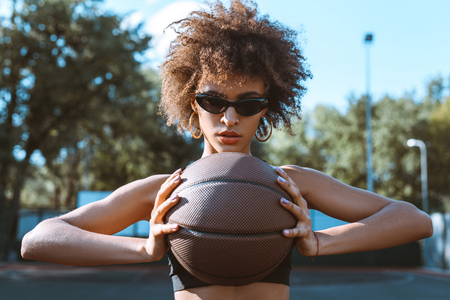 Young african-american woman in sunglasses holding basketball in front of her chest