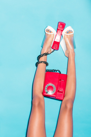 cropped view of female legs in heels holding red rotary phone,  isolated on turquoise Фото со стока - 102257269