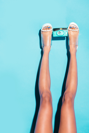 cropped view of female legs in heels holding retro photo camera,  on turquoise Archivio Fotografico