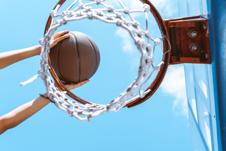 Cropped shot of female hands throwing ball into basket 스톡 콘텐츠
