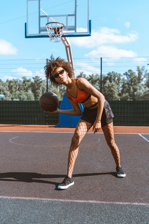 Young african-american woman in sportive attire dribbling a basketball ball at sports court
