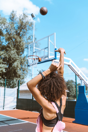 Rear view shot of young african-american woman in sports bra and pink overalls throwing a basketball ball