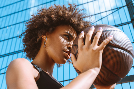 young african-american woman in sports bra holding basketball ball, adjusting her aim Stockfoto