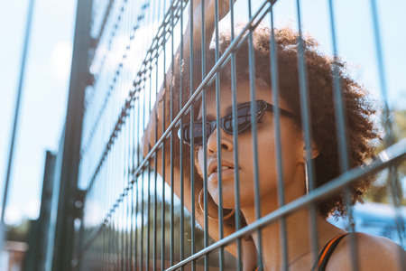 young african-american woman in sunglasses posing behind wired fencing