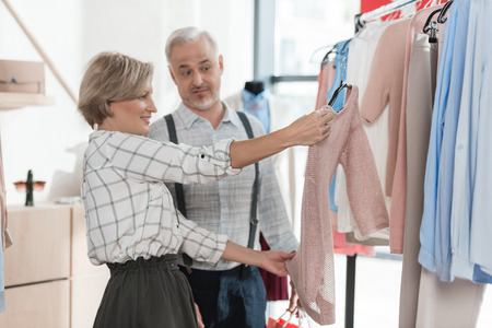 Woman showing pink shirt to husband in store