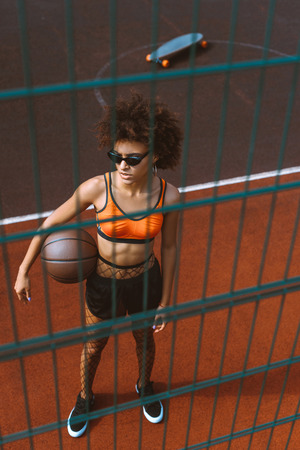 young african-american woman in sports bra and sunglasses holding a basketball ball under her arm Stok Fotoğraf