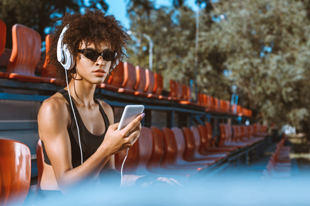 Young african-american woman in sportive attire listening to music in headphones