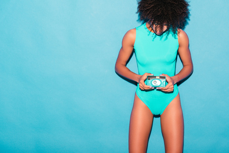 attractive african american girl posing in blue bodysuit with vintage photo camera, isolated on turquoise