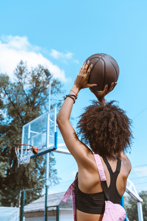 Rear view shot of young african-american woman in sports bra and pink overalls preparing to throw a basketball ball