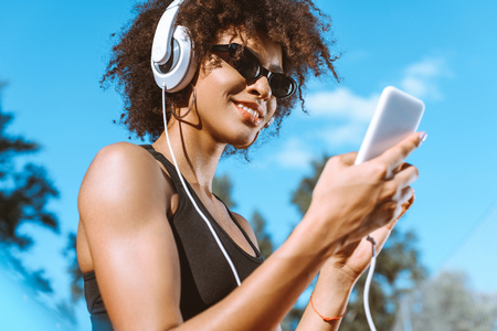 Young african-american woman in sports bra listening to music in headphones