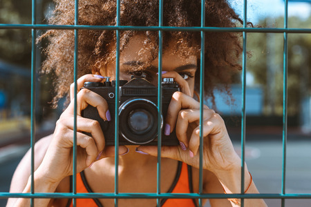 young african-american woman standing behind wired fencing and taking a picture with camera
