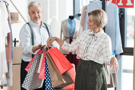 Wife giving shopping bags to husband in a store