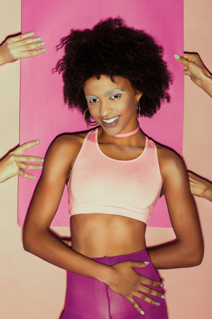 smiling african american 80s girl in pink clothes posing with pink paper behind