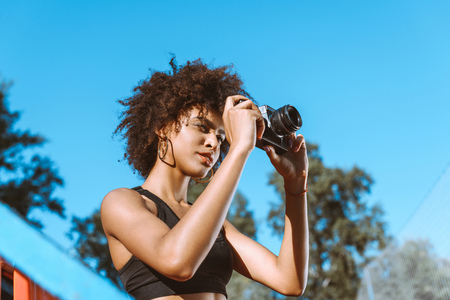 Young african-american woman in sports bra sitting in the bleachers with camera