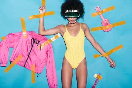 fashionable african american girl in yellow bodysuit, pink bomber and musical toys glued with scotch tape on blue