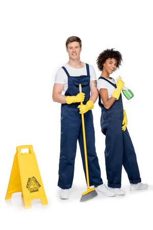 smiling multiethnic cleaners with cleaning supplies and warning sign looking at camera isolated on white Stock Photo