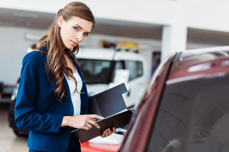 Female manager of car showroom standing with clipboard folder and looking at the camera