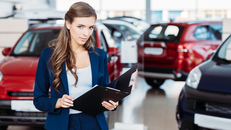 Attractive manager of car showroom standing with clipboard folder and looking at the camera
