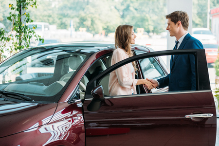 Handsome sales Manager shaking hands to customer after selling a car in showroom