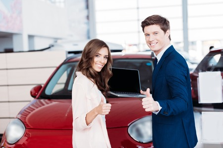 Customer and manager showing thumbs up to the camera in car showroom Stockfoto - 102361232
