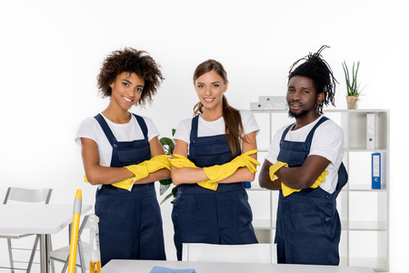 multiethnic group of professional cleaners in rubber gloves standing with crossed arms and smiling at camera Imagens