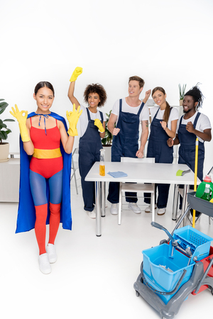 happy multiethnic group of professional cleaners working together while girl in superhero costume showing ok sign