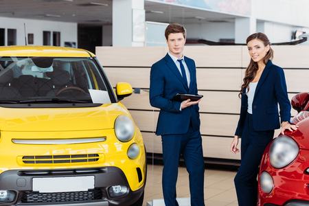 Sales managers posing in a car showroom and looking at camera