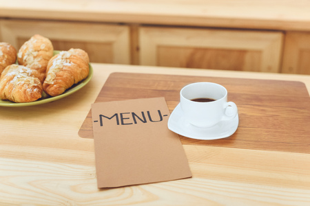 close-up view of cup of coffee, menu and croissants on table in cafe Stock Photo