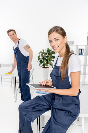 smiling female cleaner using digital tablet while male colleague with rag working behind Imagens