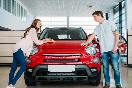 Couple standing and leaning on red car in car showroom Stockfoto