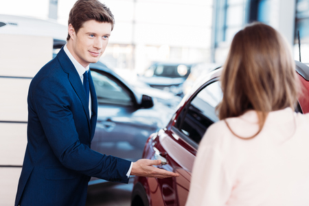 Manager inviting customer sit into a car for test-drive   Banco de Imagens