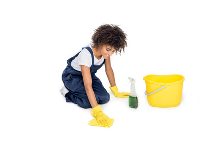 african american cleaner in uniform tidying floor with cleanser and duster isolated on white