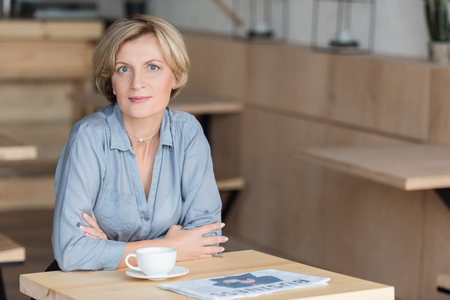 Woman posing at coffee table at cafe during her lunch time