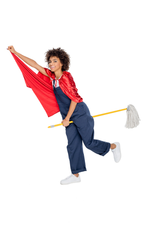 african american cleaner in uniform pretending flying on broom isolated on white