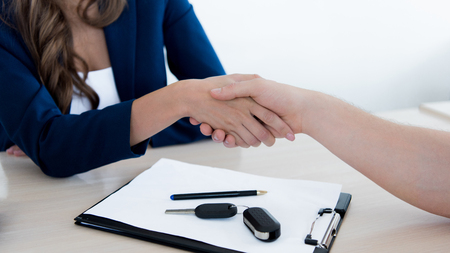Cropped image of customer and sales manager shaking hands after purchase Stockfoto