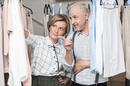 man showing to woman what clothes to choose from rack
