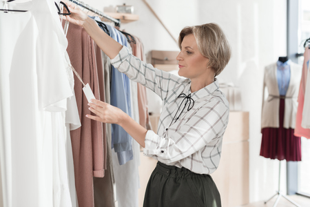 Woman looking with surprise at tag of shirt in the shop Standard-Bild - 102361679