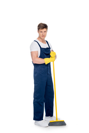 cleaner in rubber gloves and uniform with broom in hands looking at camera isolated on white Foto de archivo - 102361686