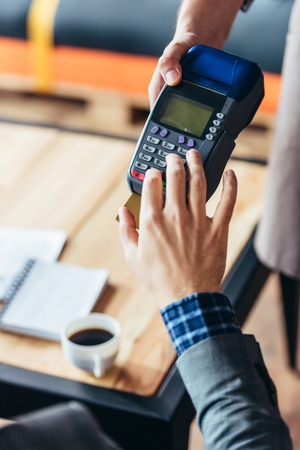 cropped shot of waiter holding payment terminal and customer using device