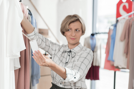 Woman looking with surprise at tag on shirt in the store