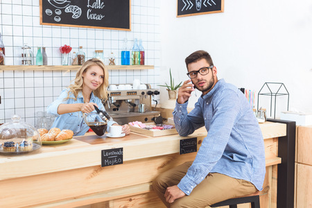 smiling young waitress pouring coffee to handsome client in eyeglasses