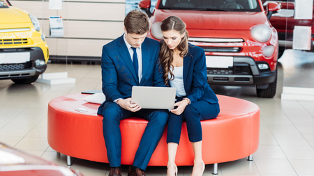 Male and female managers of car showroom sitting with a laptop on red soft bench