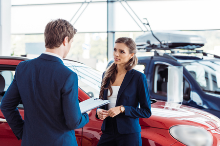 Female and male managers of car showroom standing and talking about work