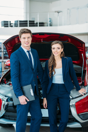 Sales managers posing in a car showroom near car with open hood