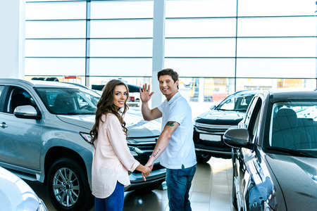 Man waving a hand and holding hands with his girlfriend in a car showroom